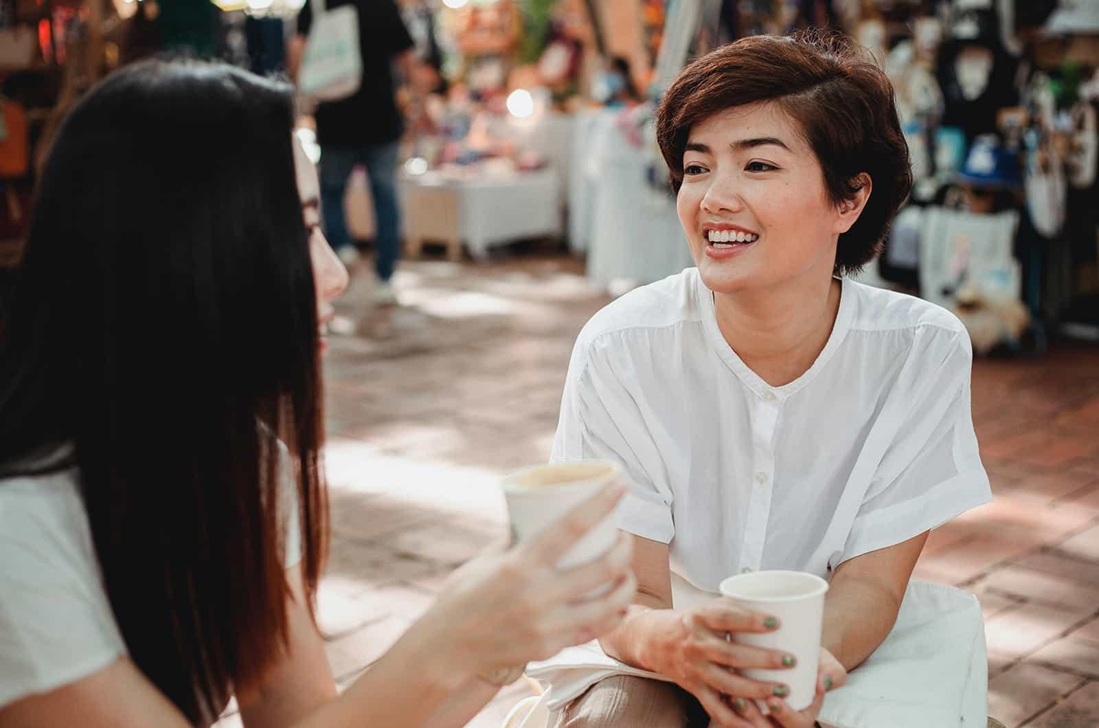 zwei Freundinnen unterhalten sich beim gemeinsamen Kaffeetrinken auf der Straße