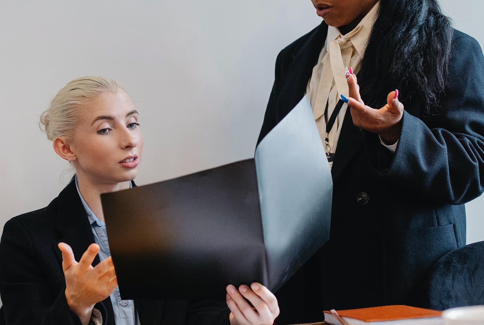 zwei Kolleginnen diskutieren über die Arbeit im Büro