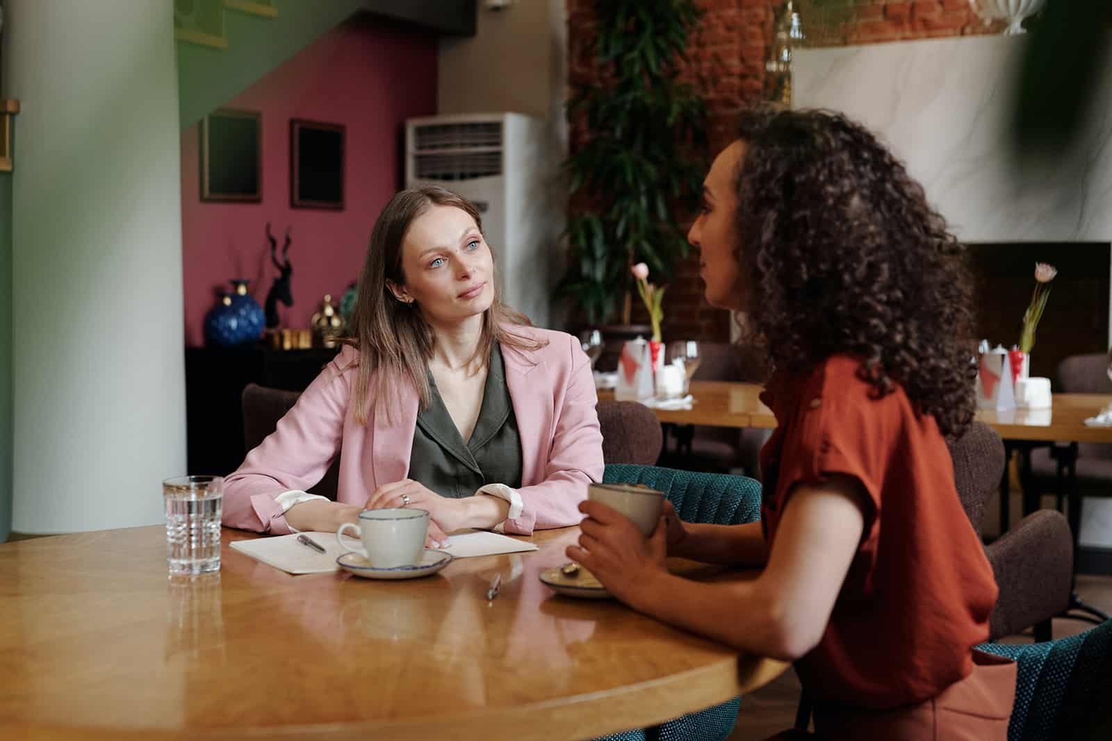 zwei Kolleginnen unterhalten sich während einer Pause beim gemeinsamen Kaffeetrinken