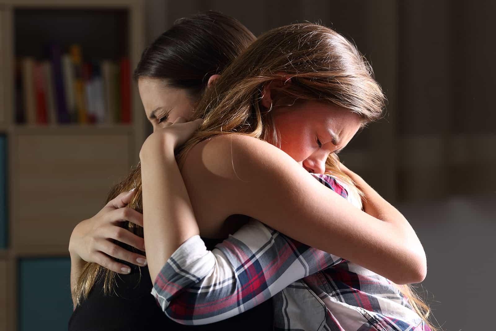 zwei traurige Frauen, die sich umarmen und zusammen weinen