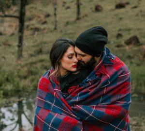 ein liebendes Paar bedeckt mit einer Decke, die in der Natur steht