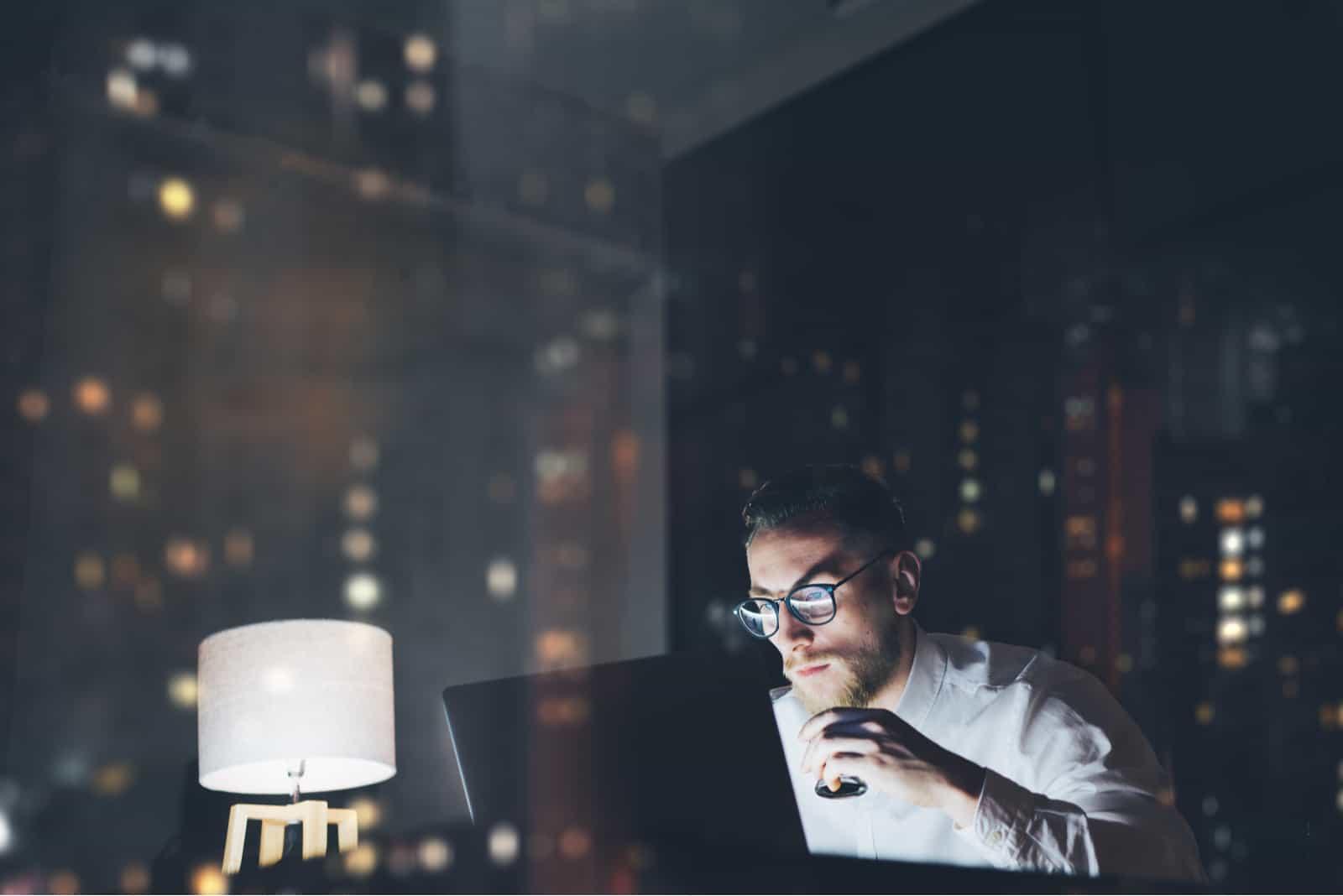 Abends arbeitet ein Mann hinter einem Laptop im Büro
