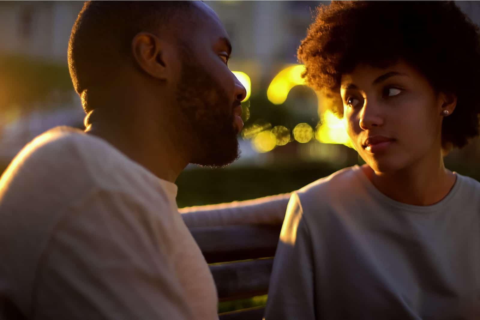 Abends sitzt ein Paar auf einer Parkbank und unterhält sich
