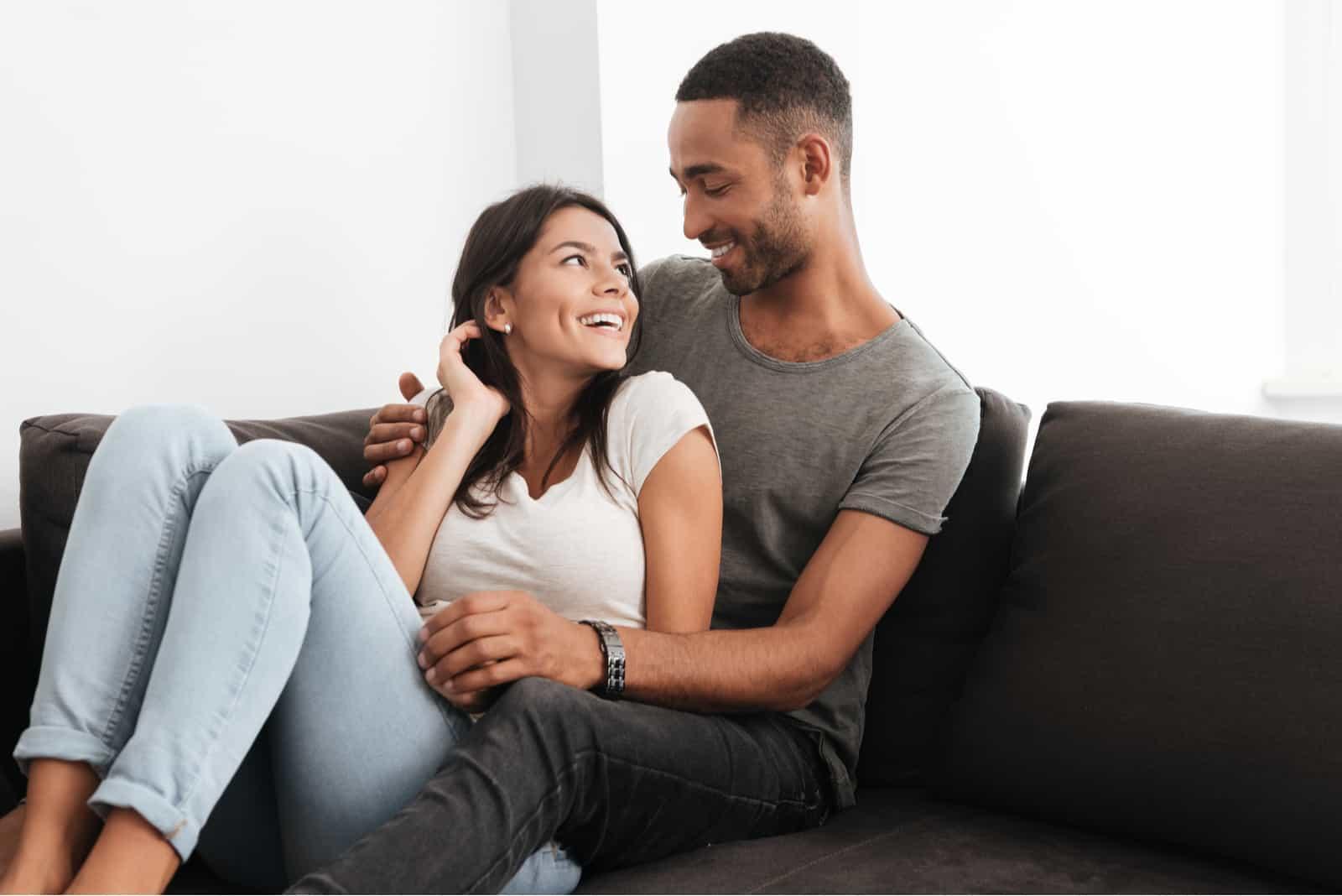Das glückliche Paar sitzt auf dem Sofa und umarmt sich
