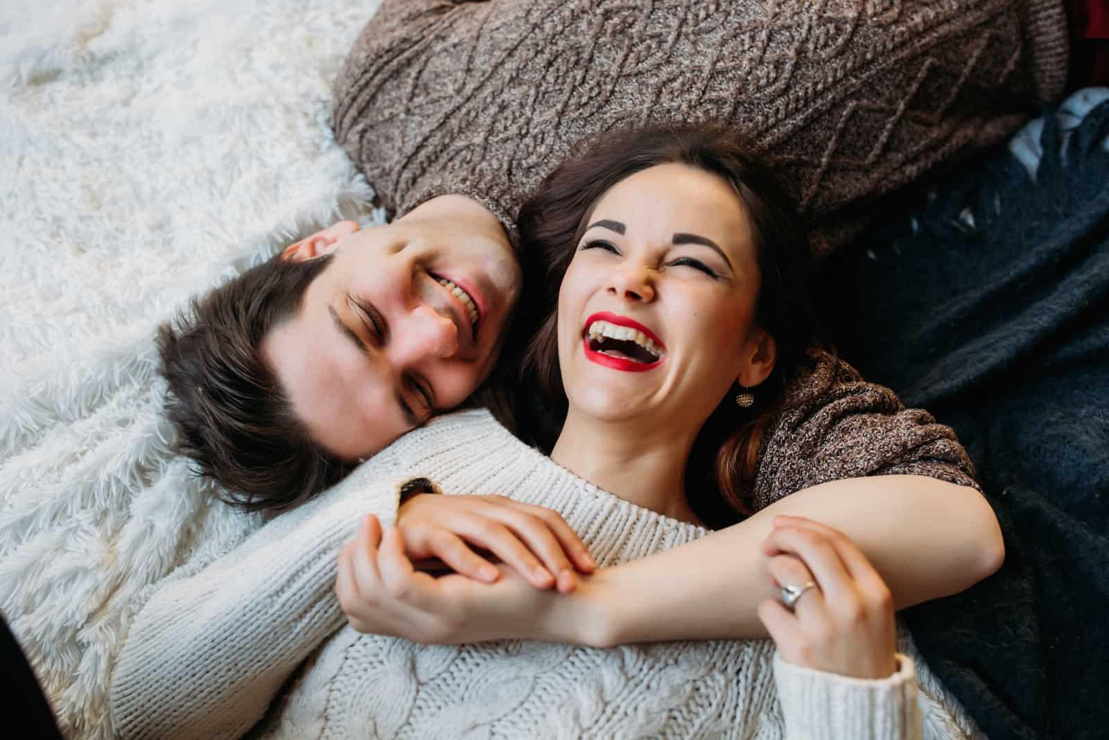 Das lächelnde Paar liegt lachend und umarmend da