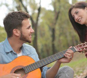 Ein Mann spielt einer lächelnden Frau Gitarre