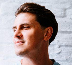ein schöner und hübscher junger Mann in einem blauen T-Shirt