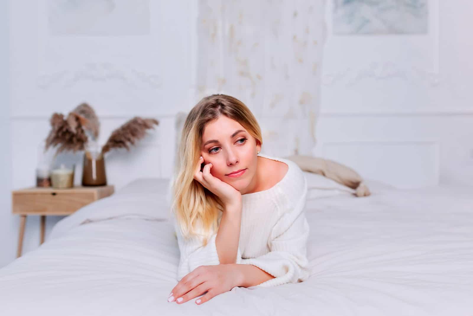 Die Blondine liegt auf dem Bett und denkt nach