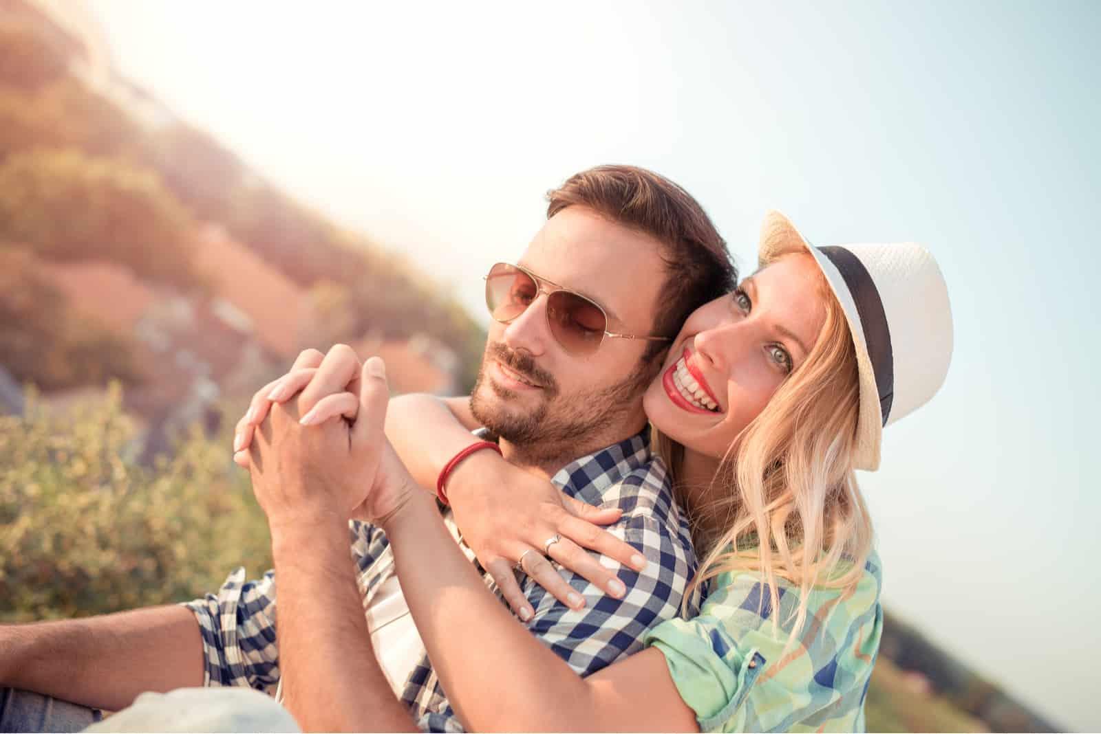 Die überglückliche Blondine umarmt sich hinter ihrem Freund