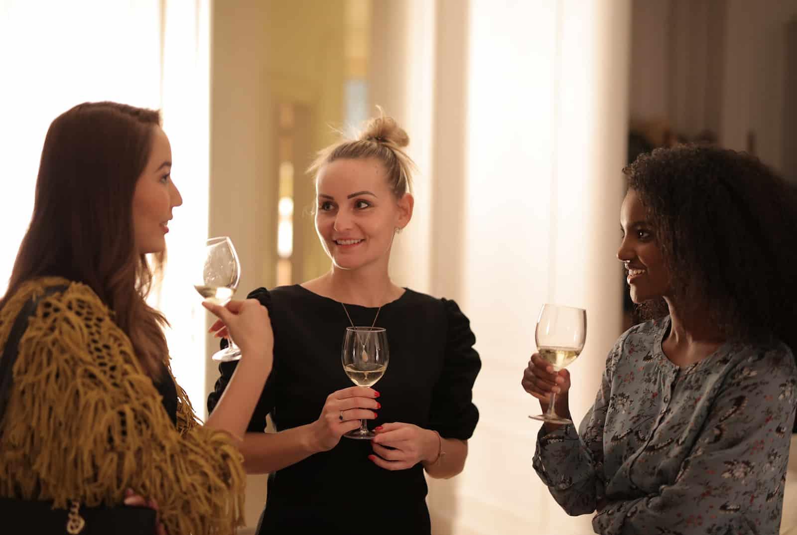 Drei Frauen unterhalten sich und halten ein Trinkglas, während sie auf der Party stehen