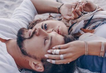 Ein junges Paar liegt im Sand und küsst sich