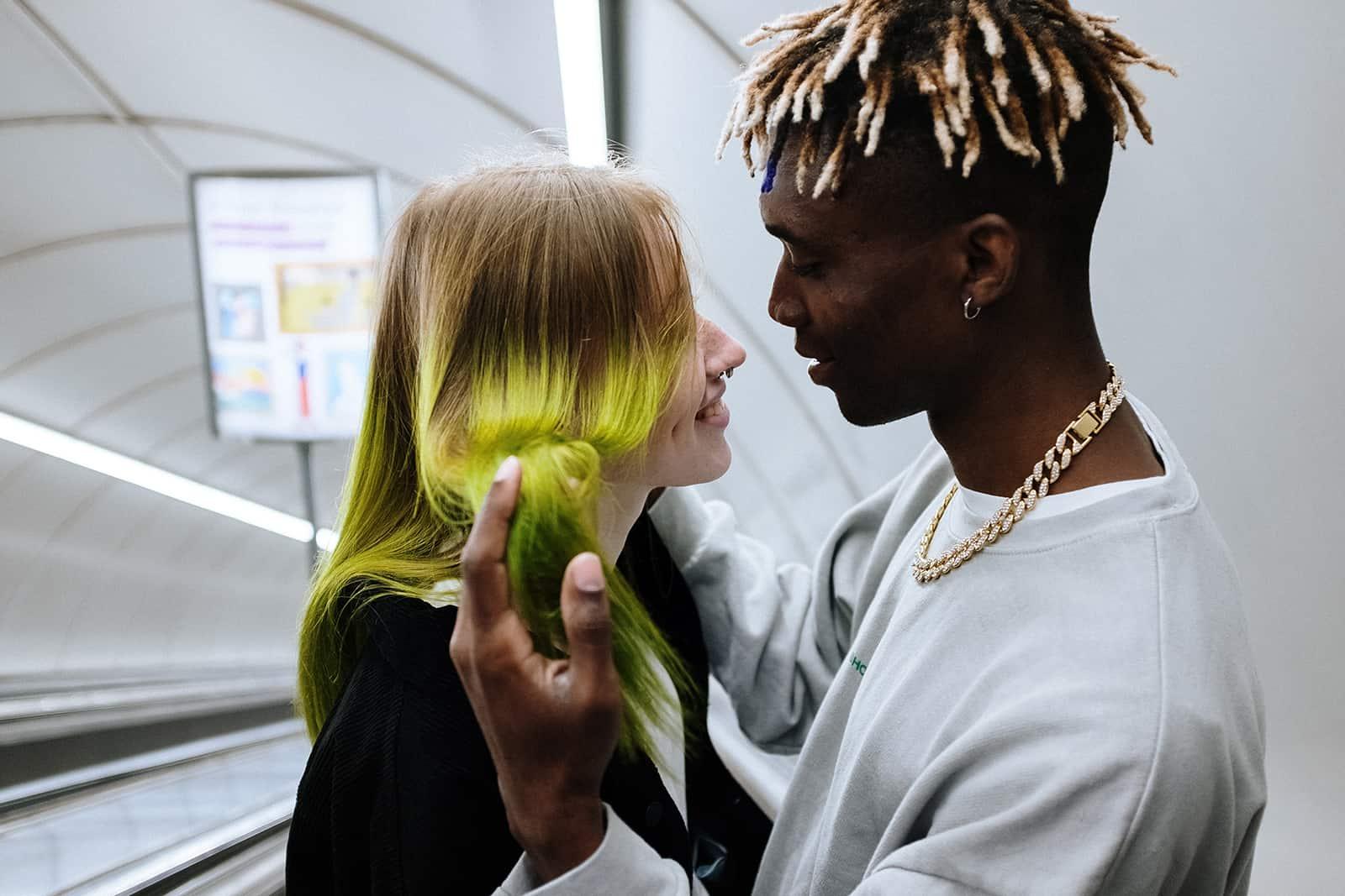 Ein Mann berührt die Haare seiner Freundin, während er sich gegenübersteht