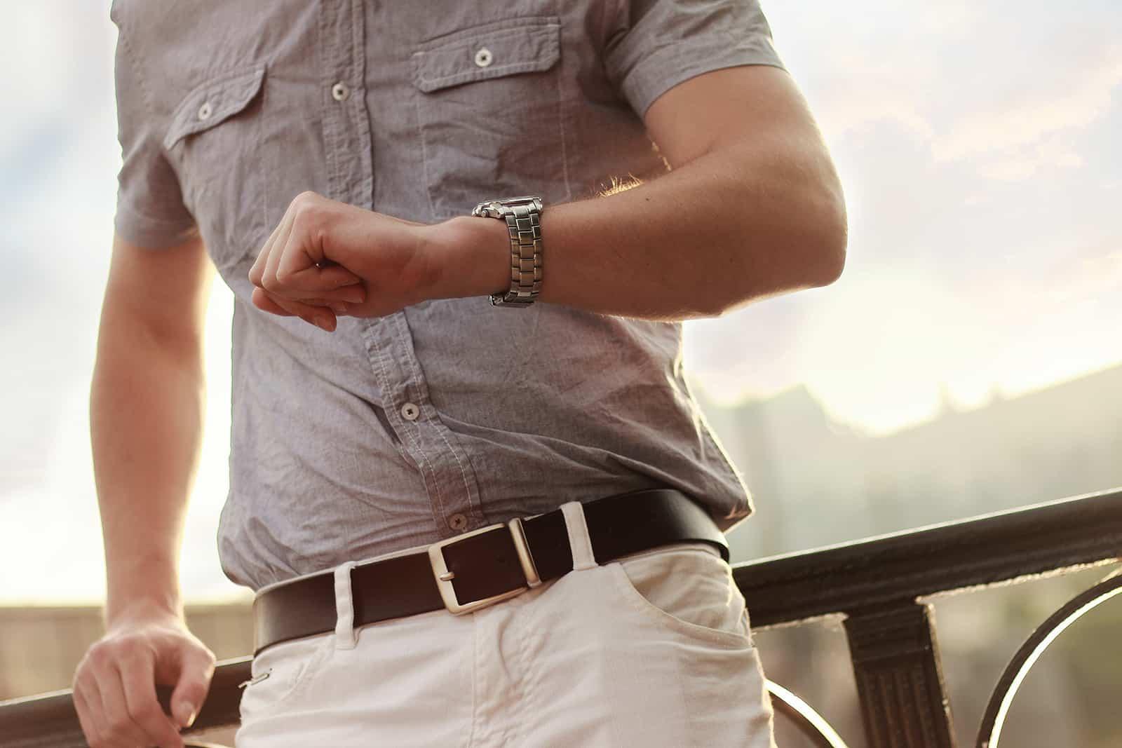 Ein Mann sah auf einer Armbanduhr auf die Uhr und lehnte sich an den Zaun