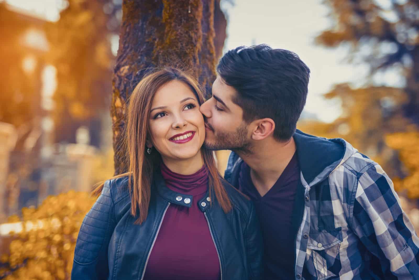 Ein Mann draußen küsst die Wange einer lächelnden Frau
