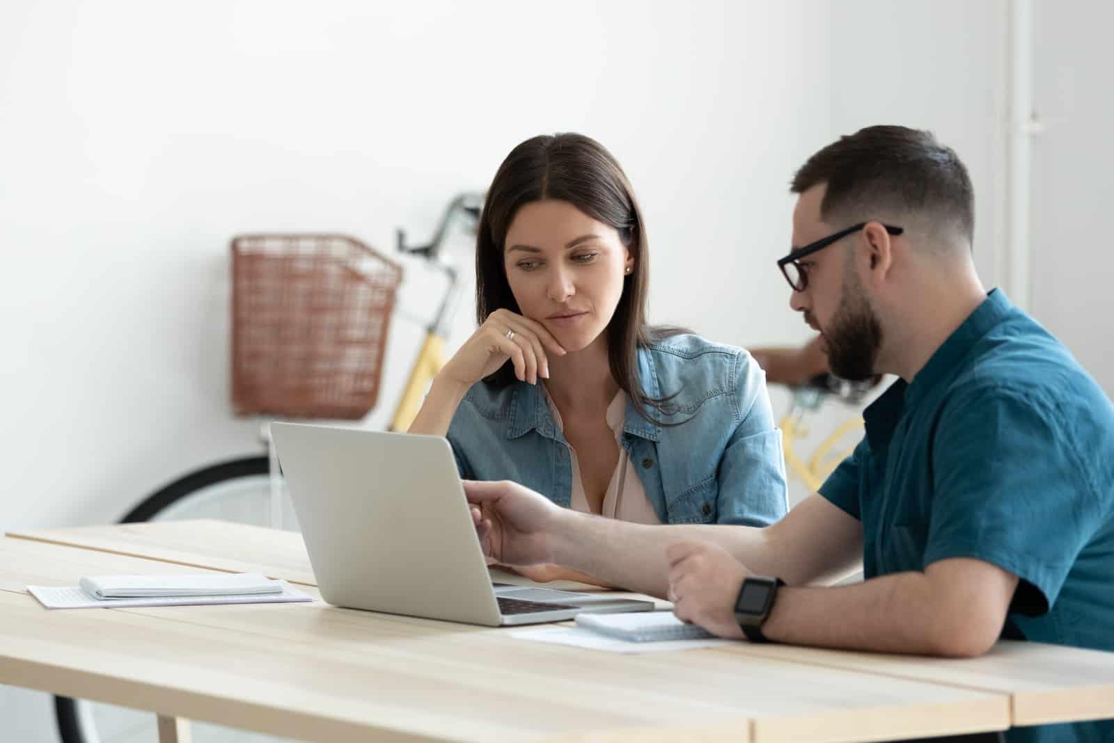 Ein Mann erklärt einer Frau auf einem Laptop etwas