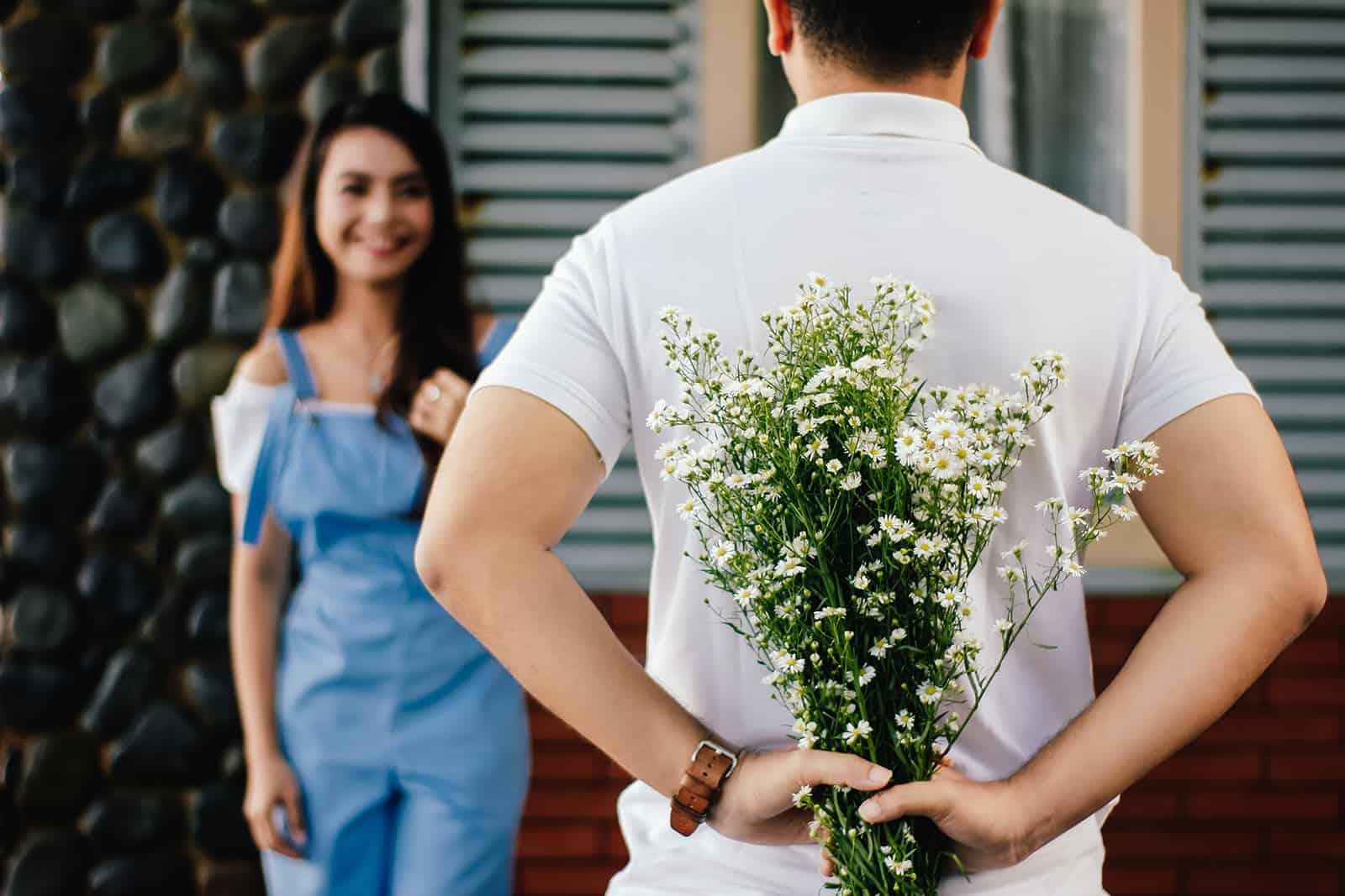 Ein Mann hält Blumen hinter seinem Rücken und steht vor einer lächelnden Frau