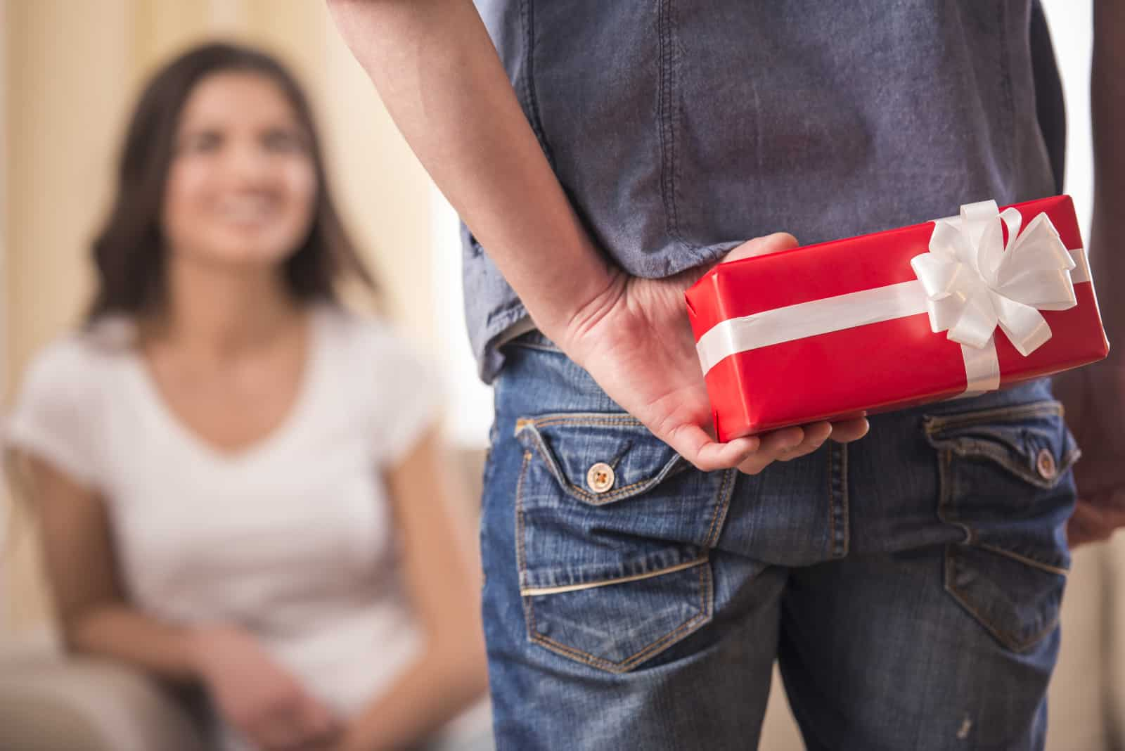 Ein Mann hält ein Geschenk für ein Mädchen hinter seinem Rücken
