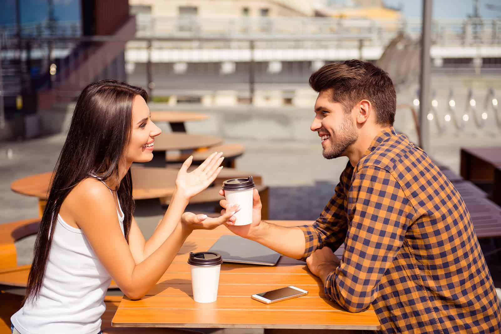 Ein Mann hört einer lächelnden Frau zu, die mit ihm spricht, während sie im Café sitzt