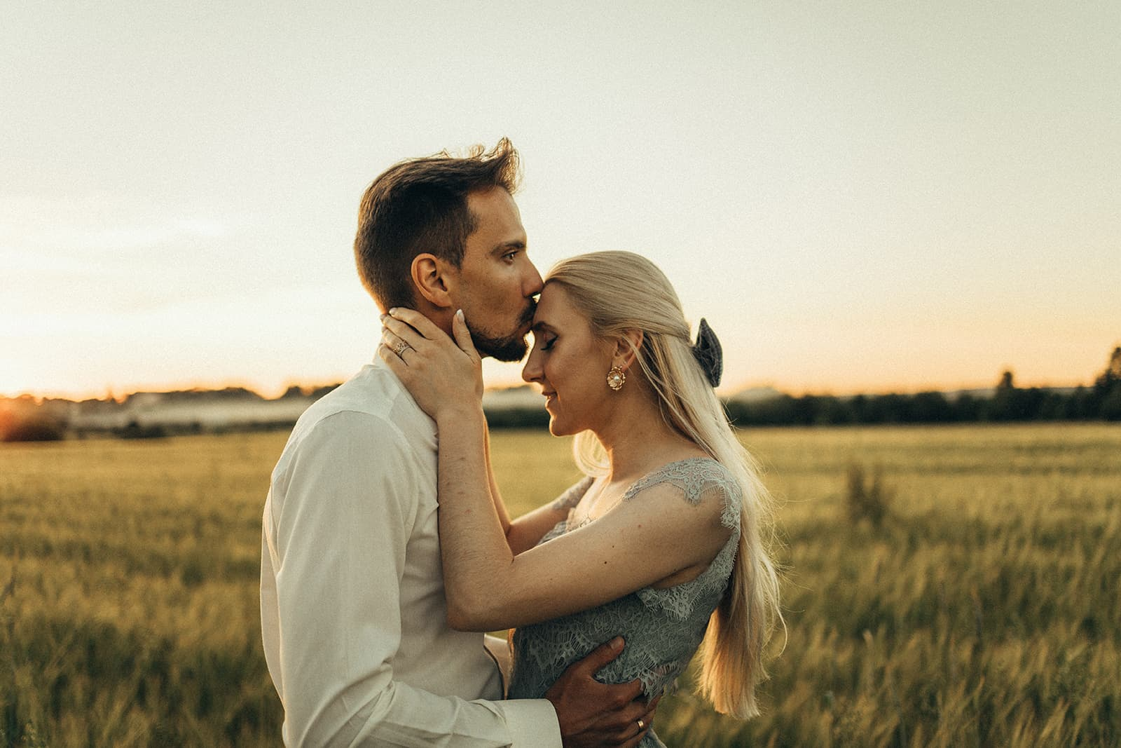 Ein Mann küsst eine Frau auf die Stirn, während er zusammen auf einem Feld steht