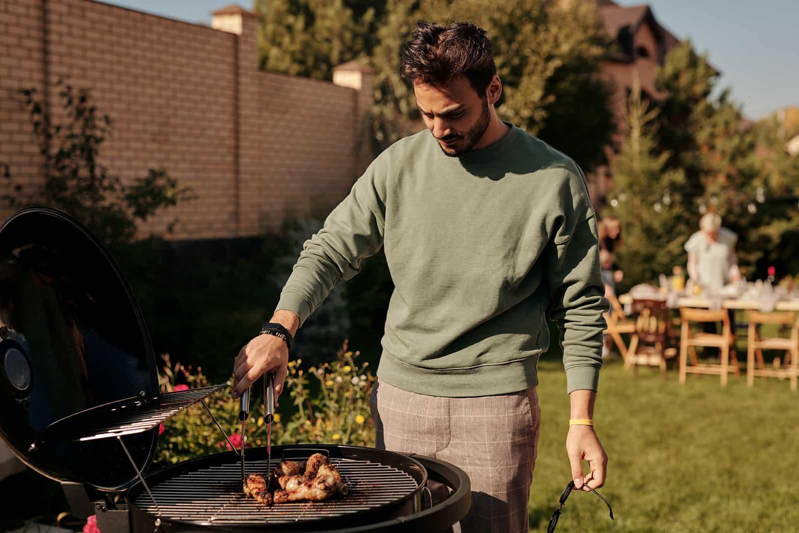 Ein Mann stand in der Nähe des Grills und bereitete Fleisch zu