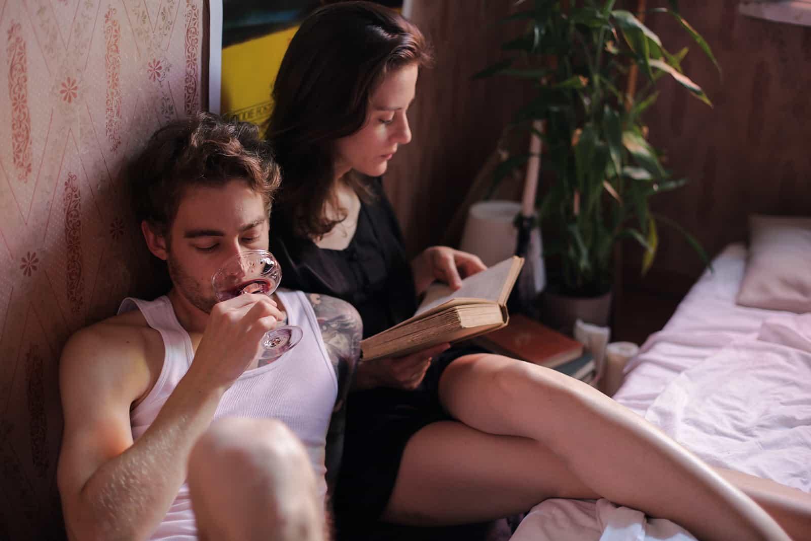 Ein Mann trinkt Wein und eine Frau liest ein Buch, während sie neben einem Bett sitzt