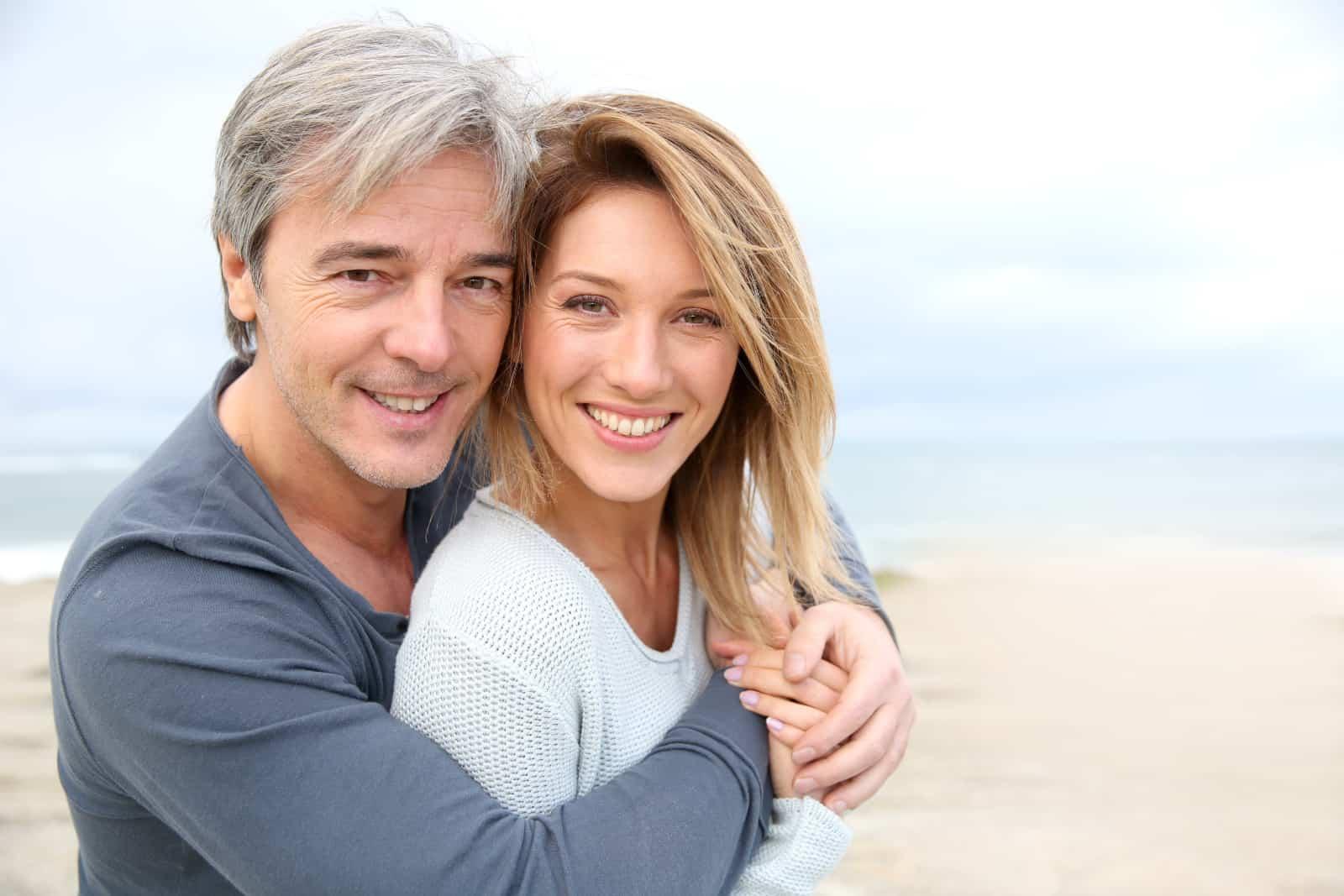 Ein Mann umarmt eine Frau am Strand