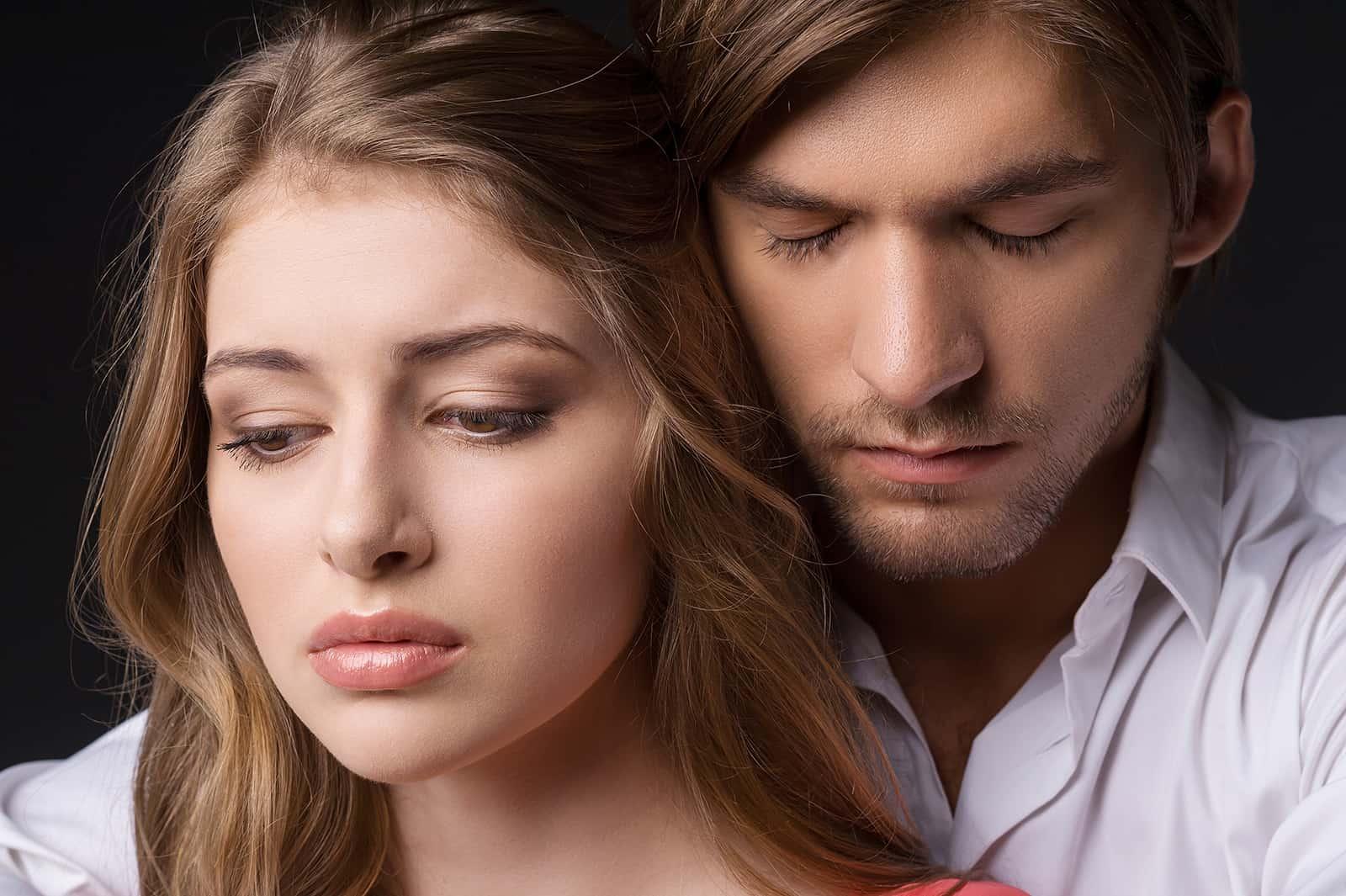 Ein Mann mit geschlossenen Augen umarmt eine traurige Frau von hinten