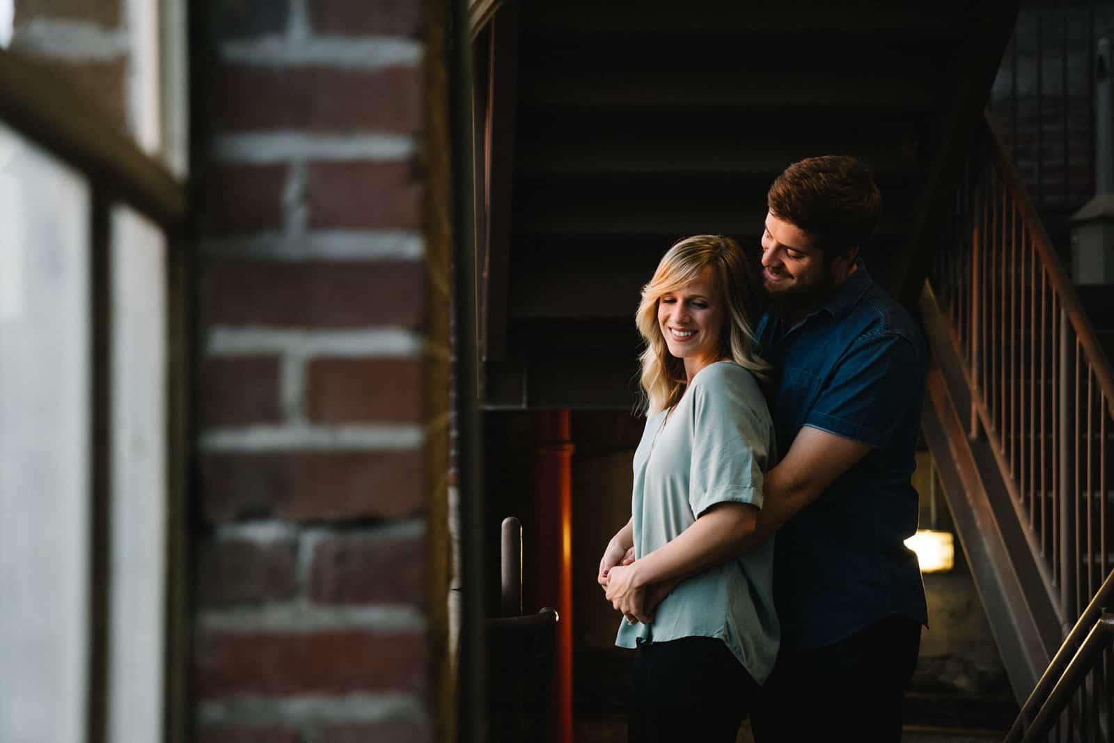 Ein Mann umarmt seine lächelnde Freundin am Fenster