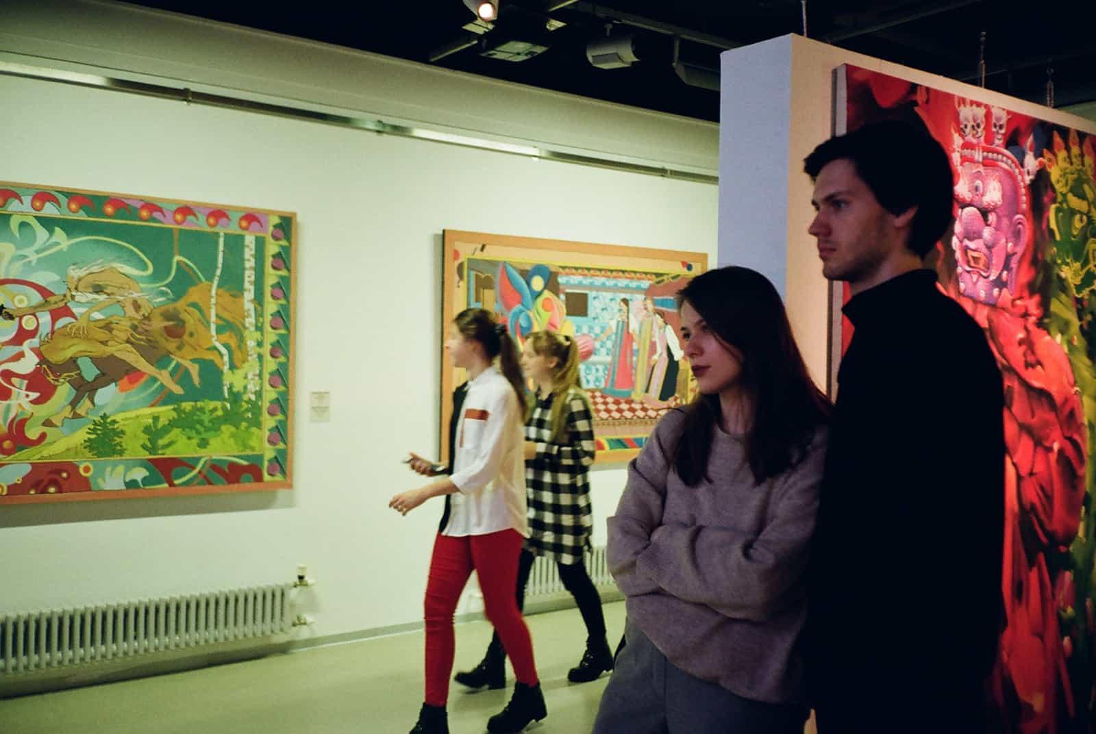 Ein Mann und eine Frau beobachten eine Bilderausstellung in der Kunstgalerie