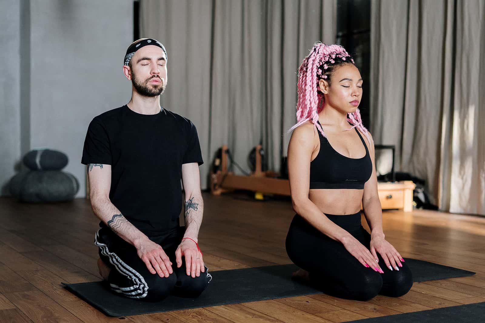 Ein Mann und eine Frau meditieren zusammen auf einer schwarzen Matte
