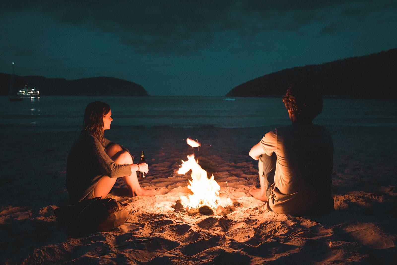 Ein Mann und eine Frau sitzen in der Nähe des Feuers am Strand
