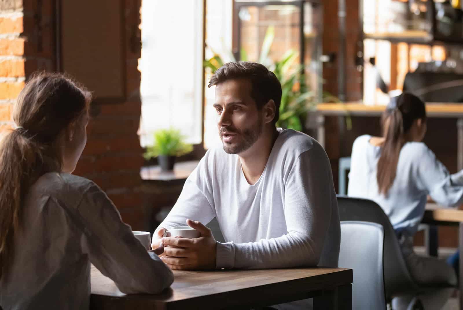 Ein Mann und eine Frau unterhalten sich während eines Speed-Dates am Tisch
