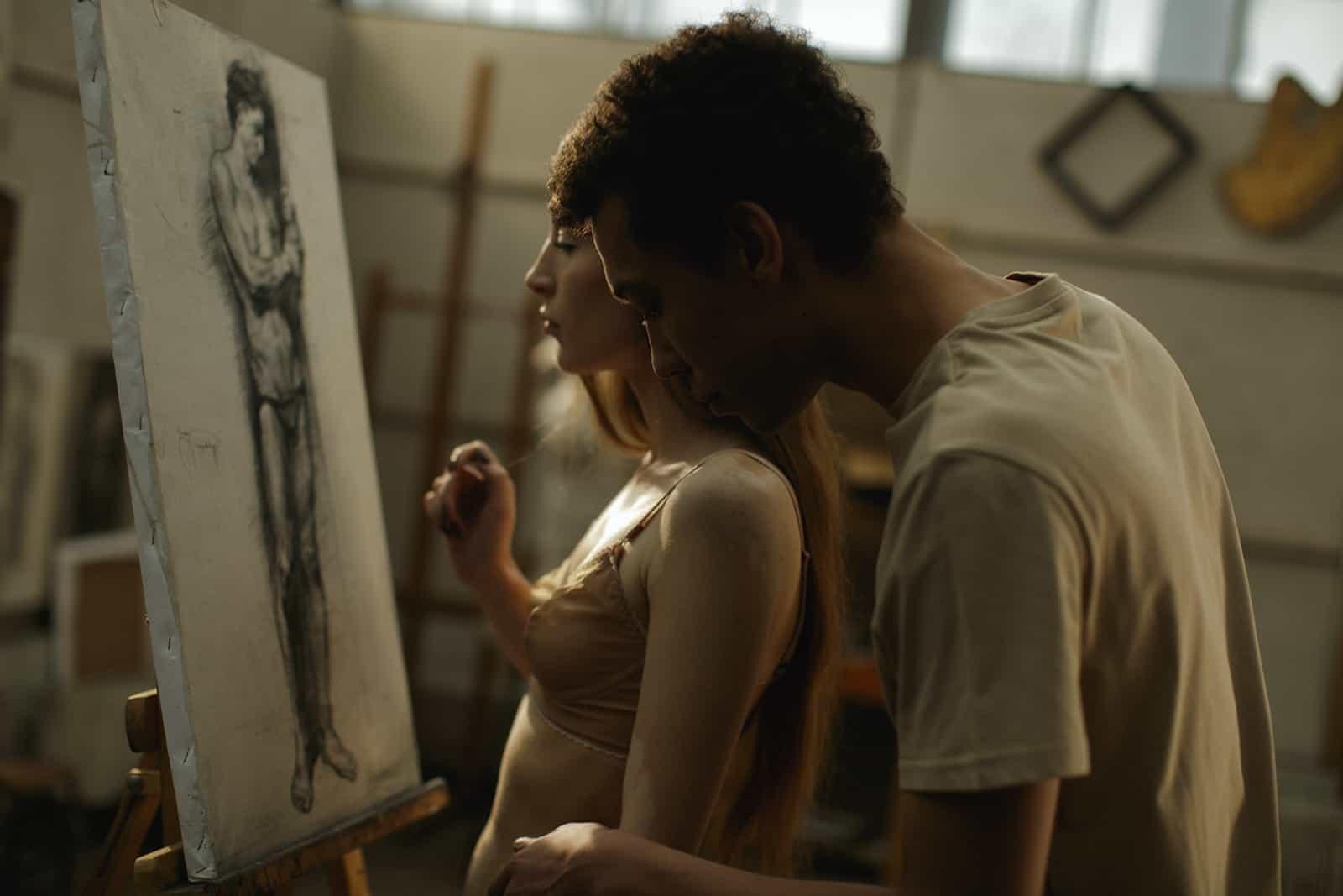Ein Mann, der einer Frau zeigt, zeichnet in einem Atelier