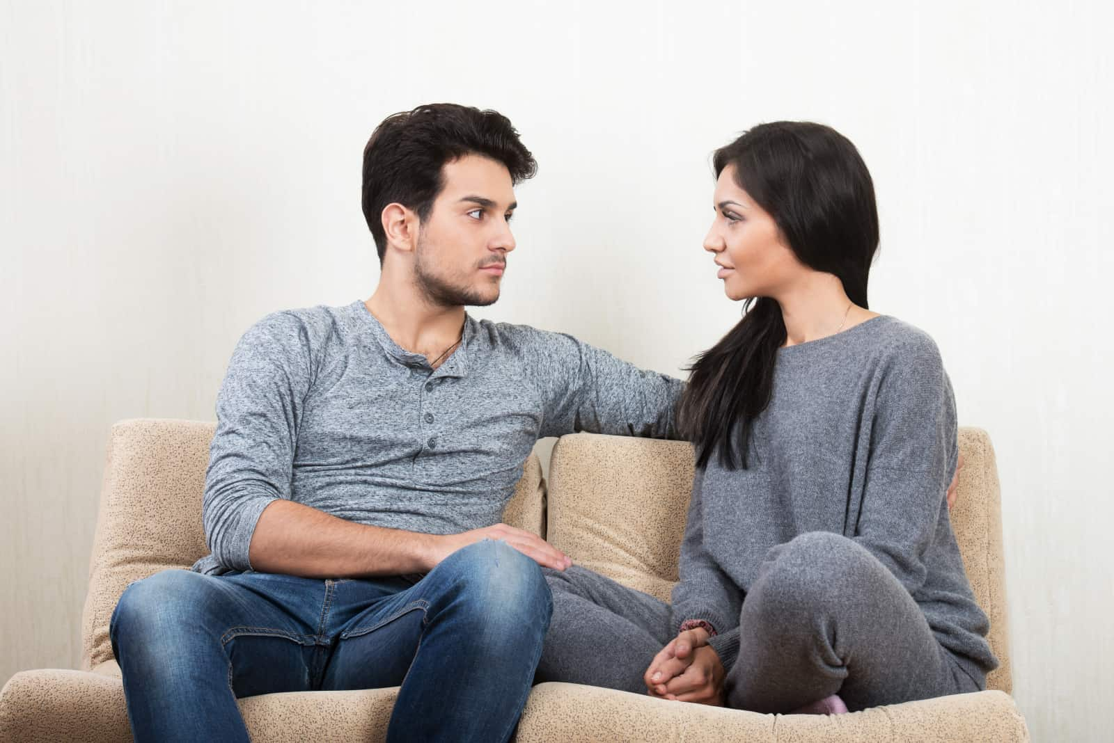 Ein Paar sitzt auf der Couch und redet