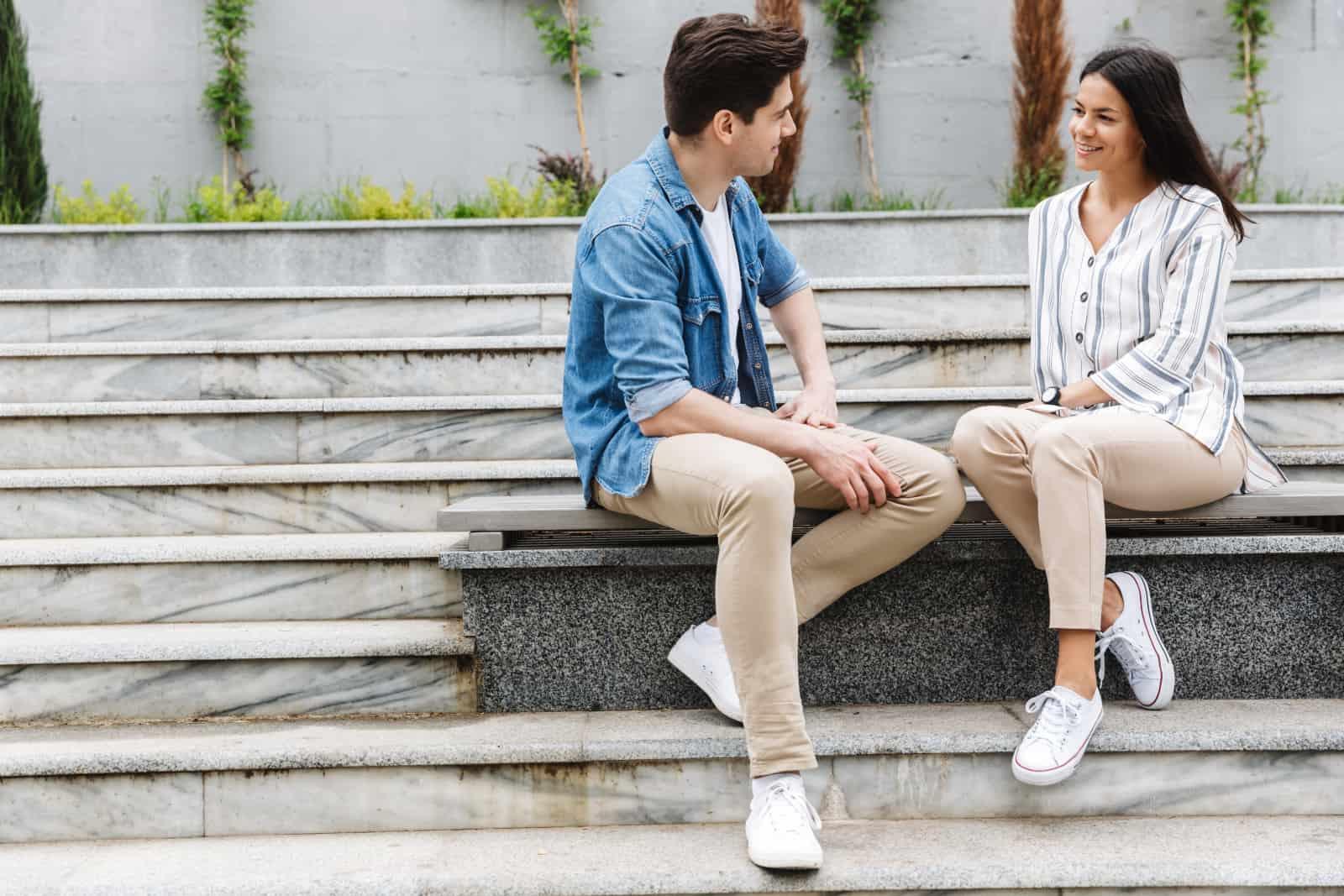Ein junges Paar sitzt im Park und redet