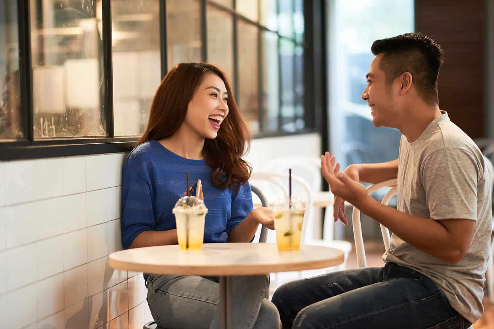 Ein lächelnder Mann und eine Frau sitzen im Café und unterhalten sich während eines Dates