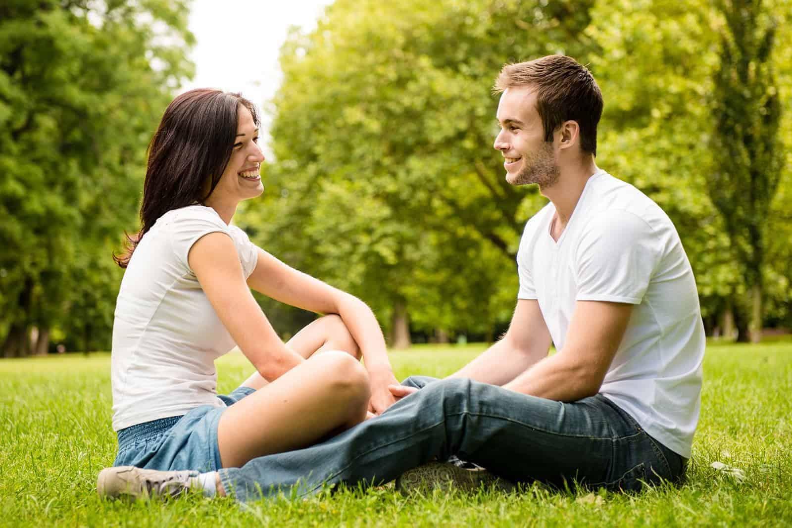 Ein lächelnder Mann und eine lächelnde Frau sitzen sich im Gras gegenüber