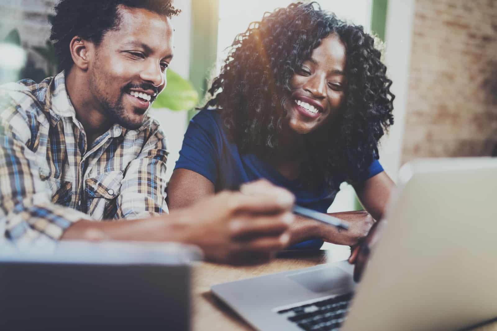 Ein lächelndes Paar benutzt einen Laptop