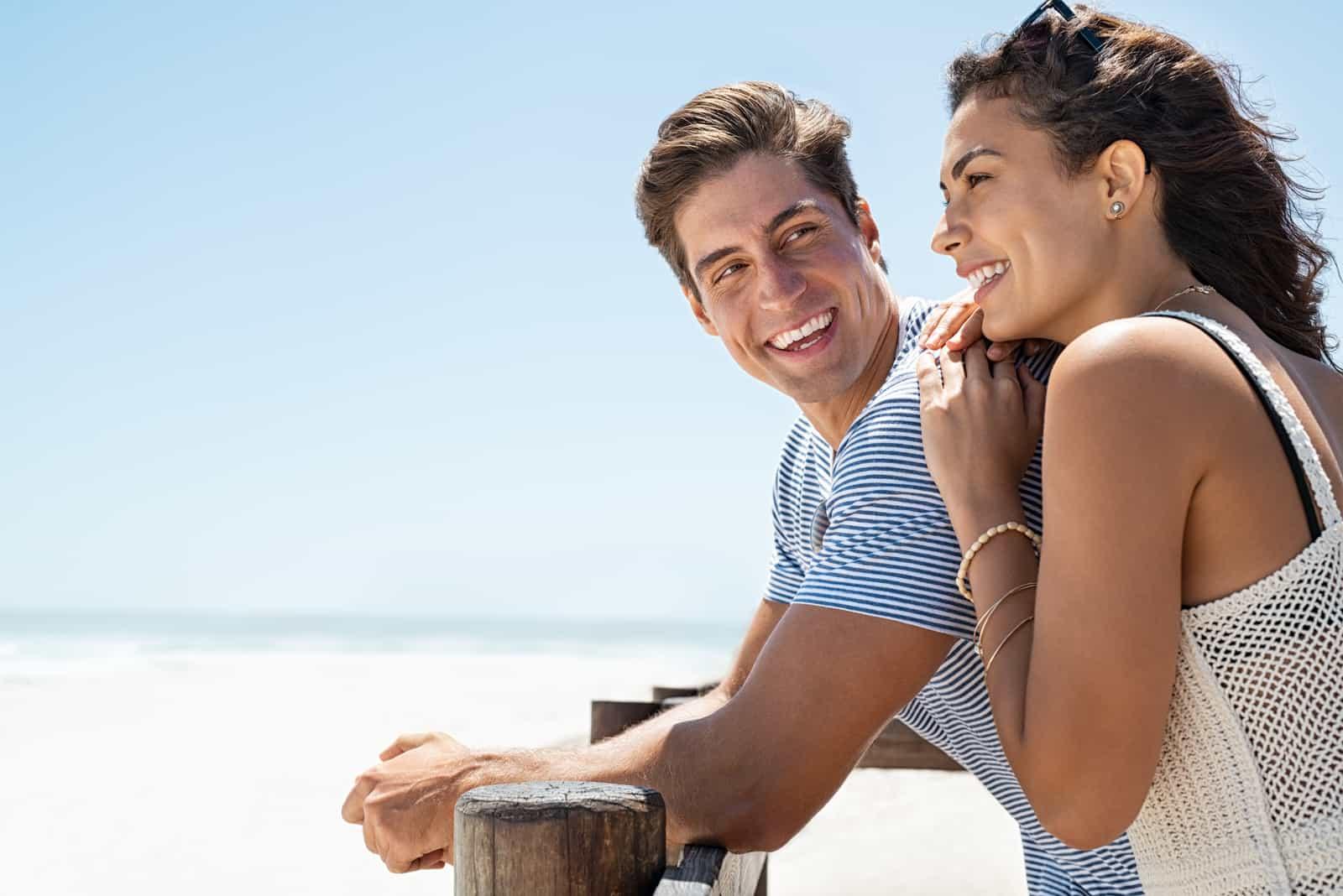 Ein lächelndes Paar, das am Strand steht und sich gegen einen Holzzaun lehnt