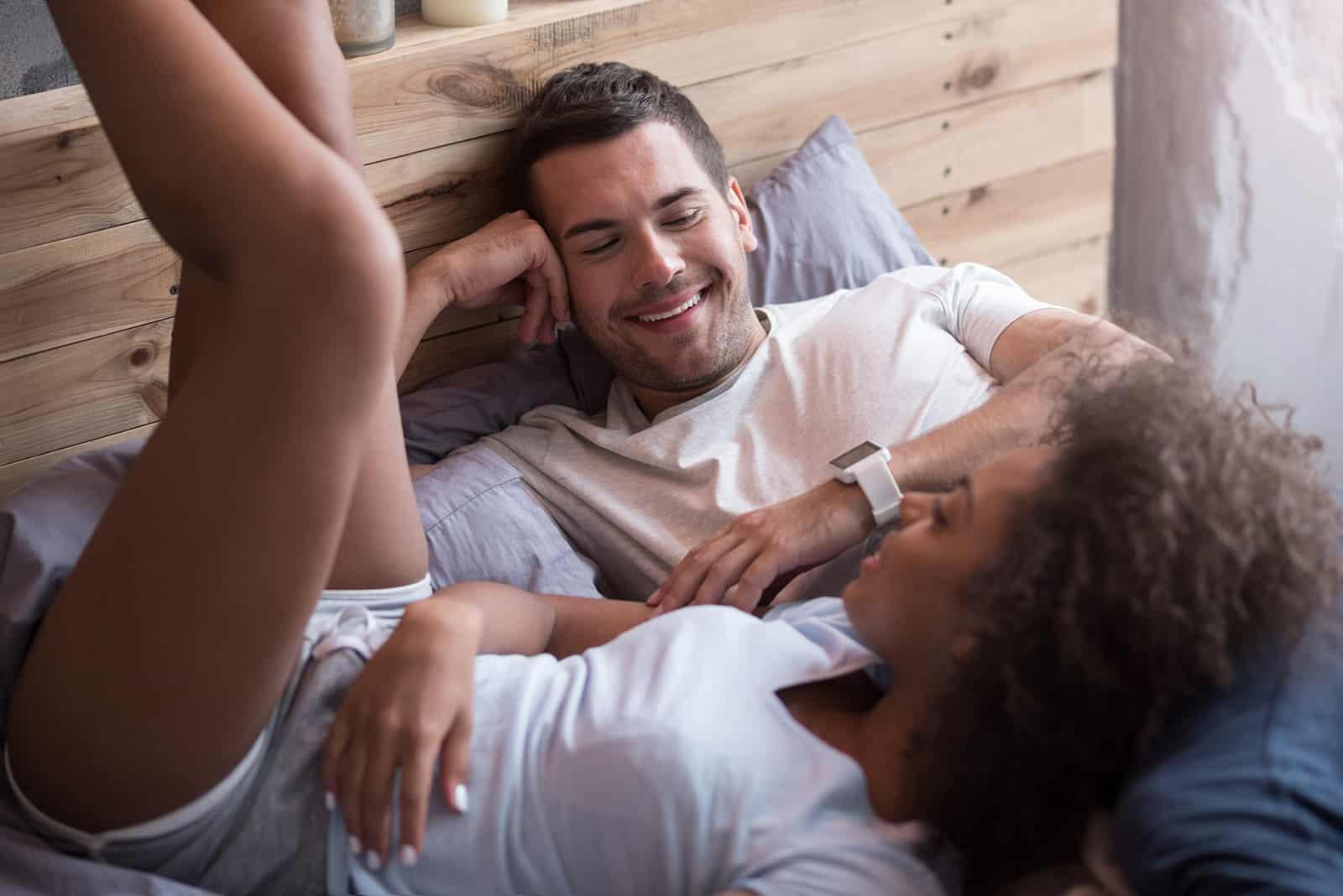 Ein lächelndes Paar, das im Bett liegt und redet