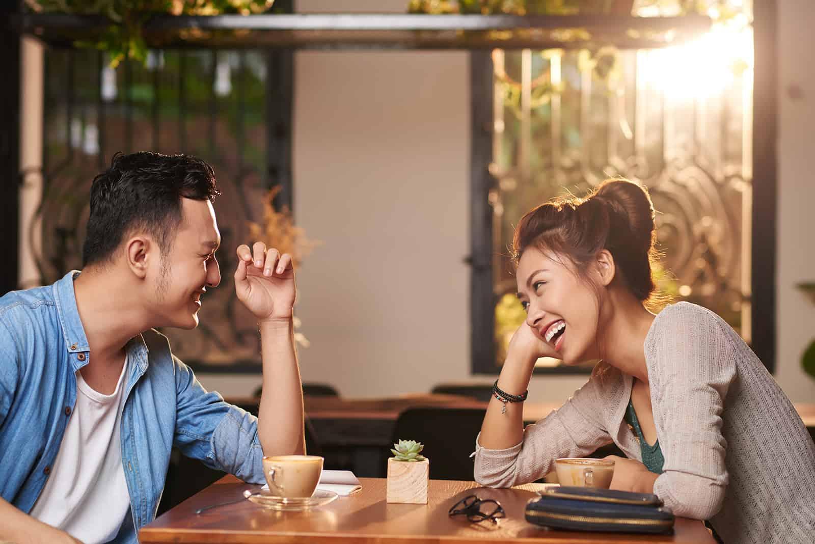 Ein lachender Mann und eine lachende Frau sitzen bei einem Date im Café