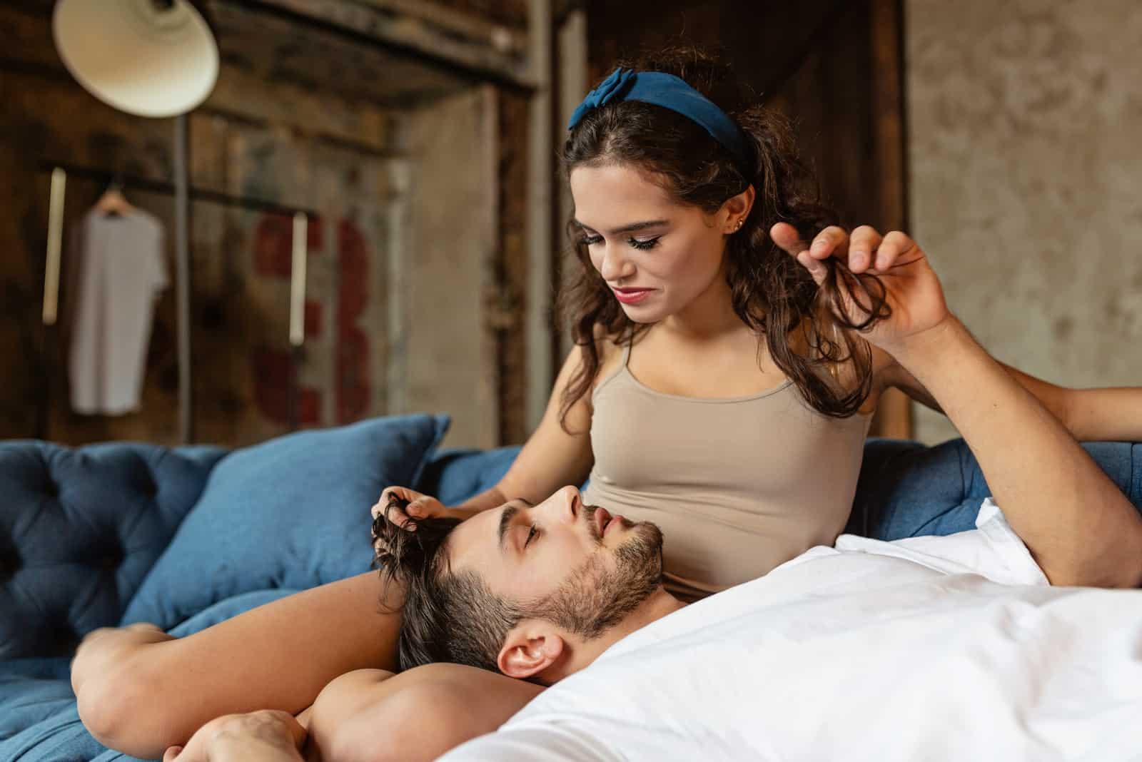 Ein liebevolles Paar auf dem Sofa redet und streichelt sich