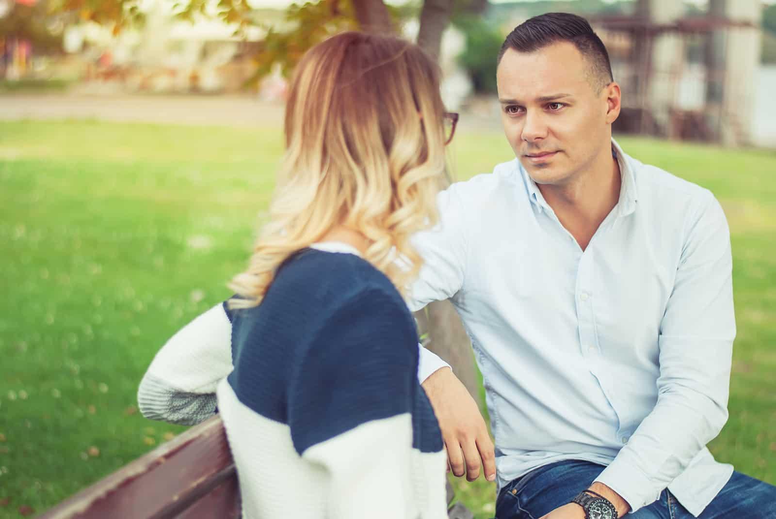 Ein trauriger Mann hört einer Frau zu, die mit ihm spricht auf der Bank im Park sitzen