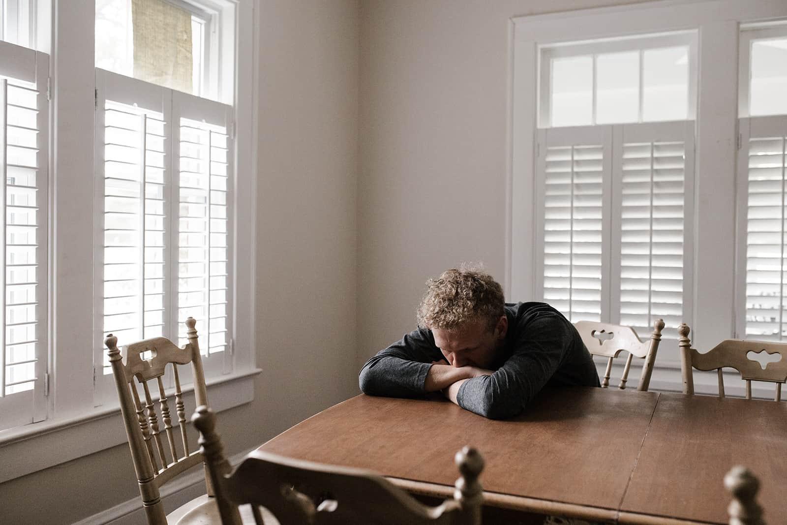 Ein trauriger Mann lehnte sich auf den Tisch im Esszimmer