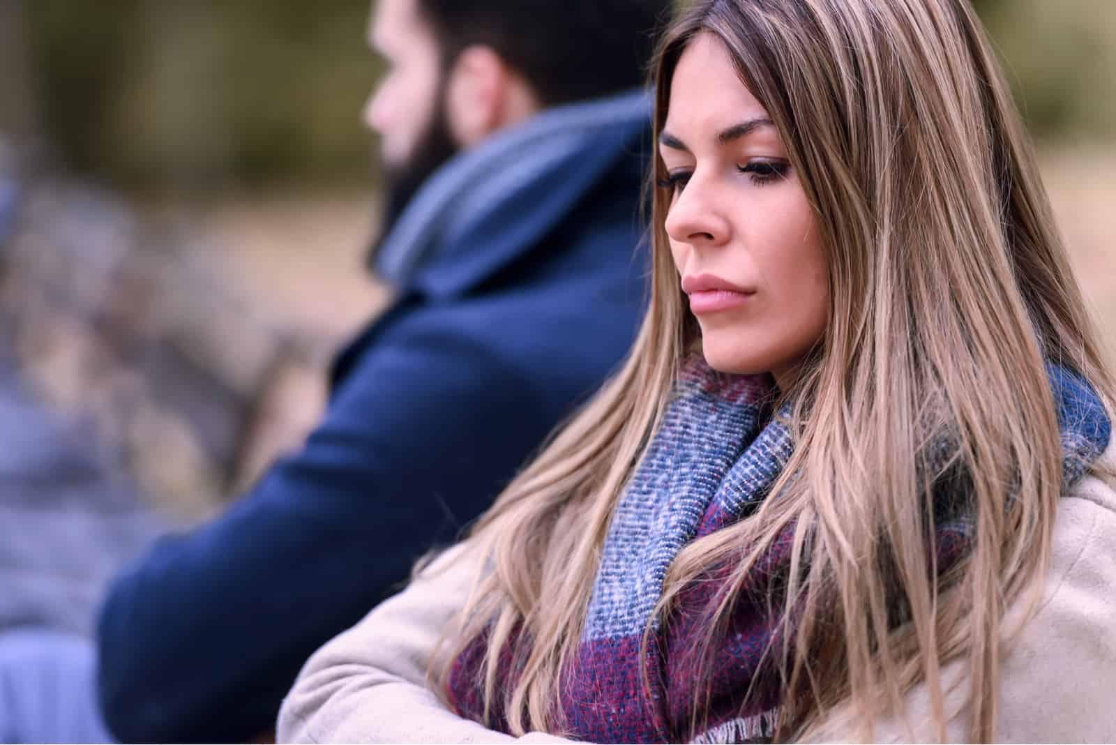 Ein trauriges Liebespaar sitzt auf einer Parkbank