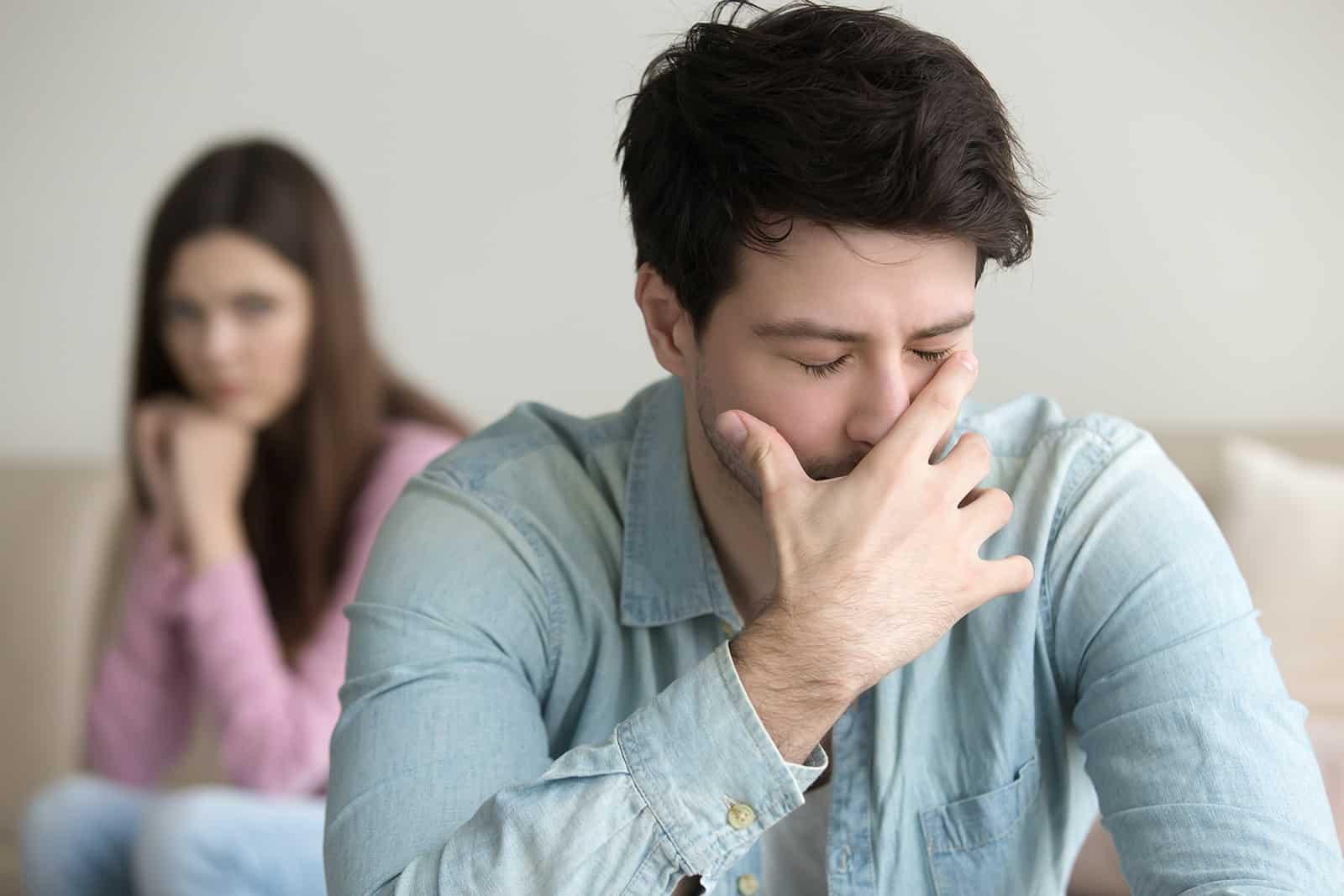 Ein verärgerter Mann bedeckte sein Gesicht mit der Hand, während eine Frau hinter ihm auf der Couch saß