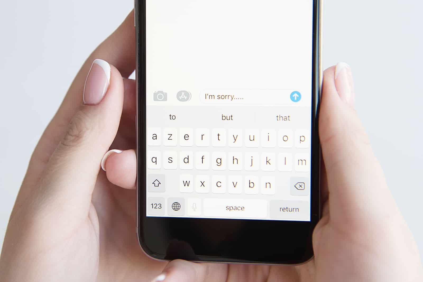 Eine Frau, die eine Nachricht auf einem Smartphone schreibt, um sich bei jemandem zu entschuldigen