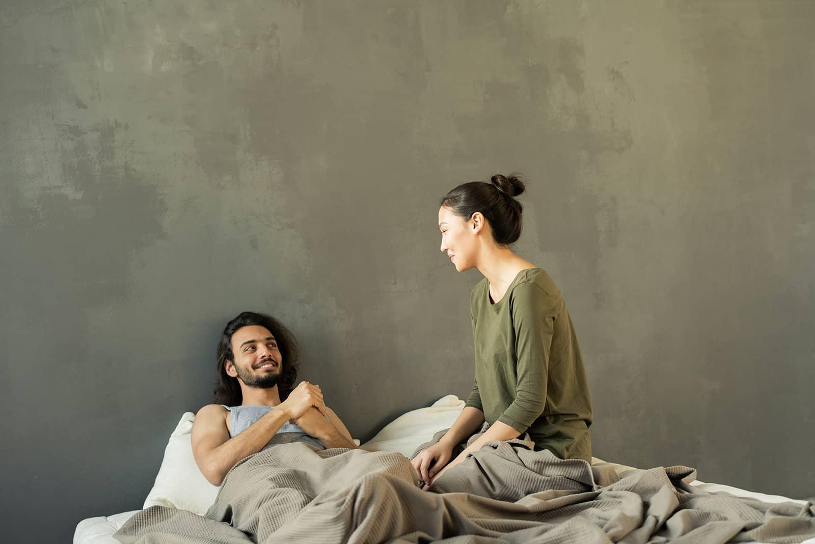 Eine Frau sitzt auf dem Bett und spricht mit einem Mann, der neben ihr liegt