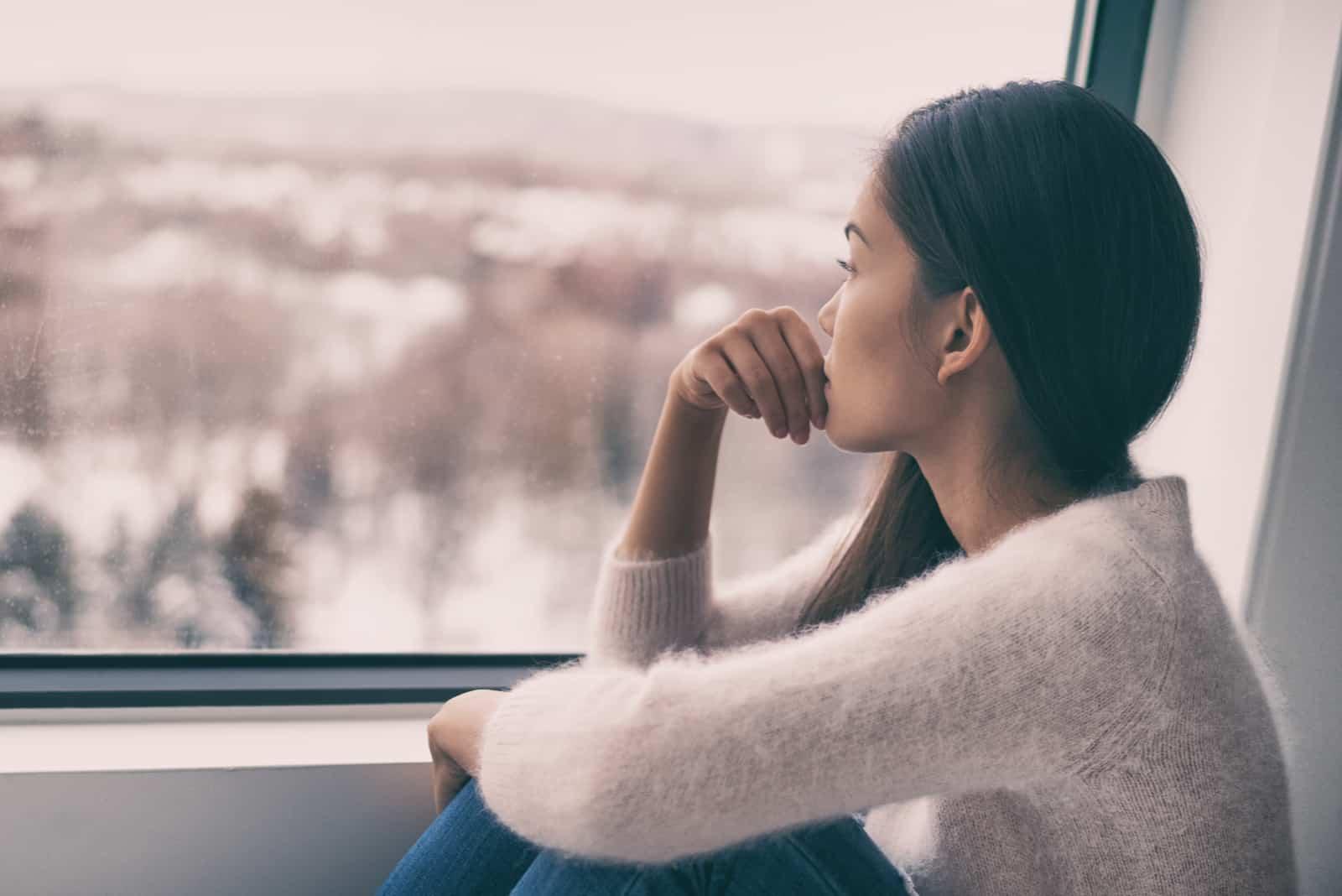 Eine nachdenkliche Frau in einem weißen Pullover sitzt am Fenster und schaut nach draußen