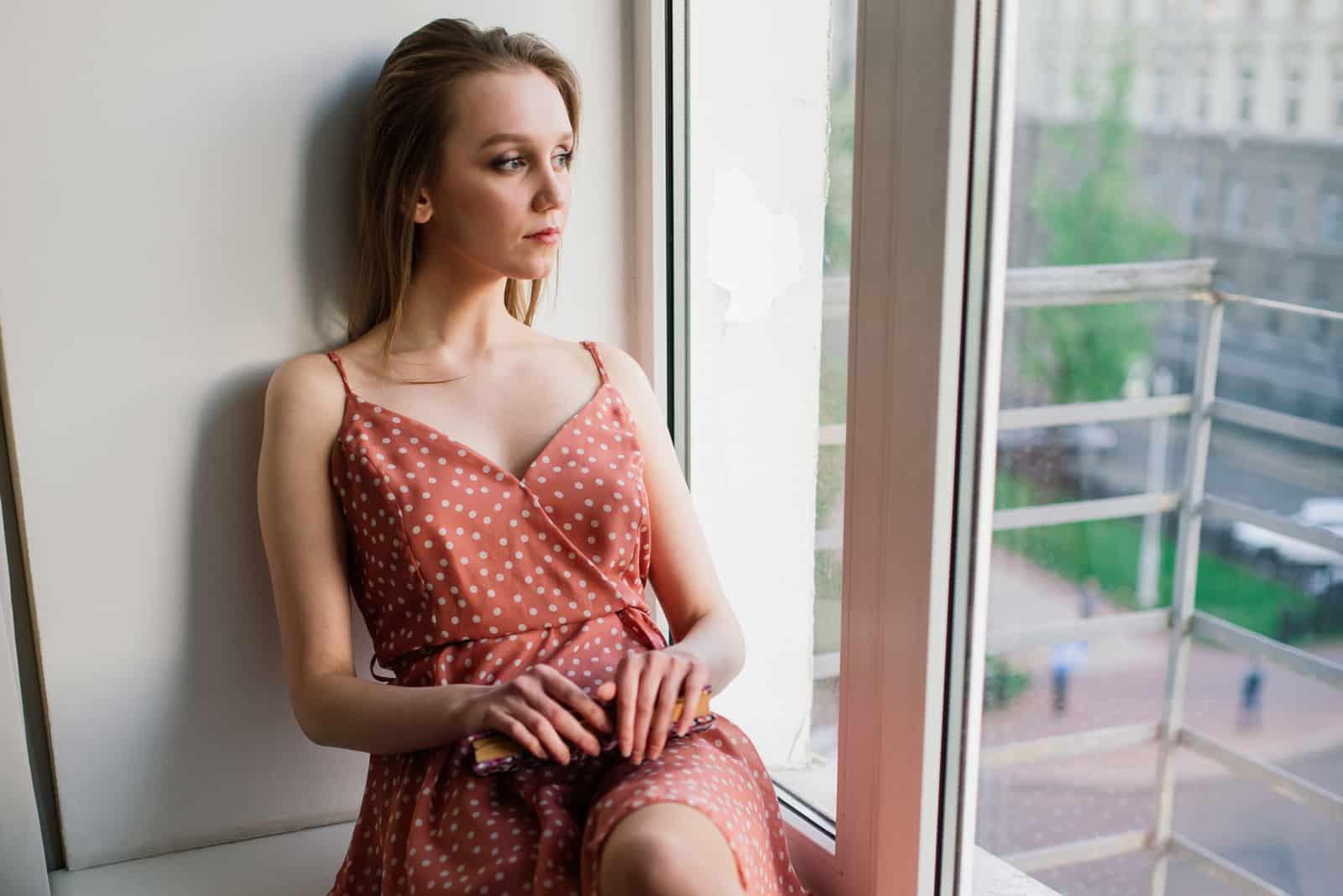 Eine schöne Blondine in einem Kleid sitzt am Fenster und schaut nach draußen